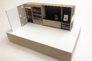 1:12 scale model of a micromarket. The model is made from laser cut gloss white acrylic and oak. It is animated with scale model food and till ans ditting on a veneered baseboard.