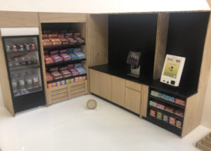 1:12 scale model of a micromarket. The model is made from laser cut gloss white acrylic and oak. It is animated with scale model food.
