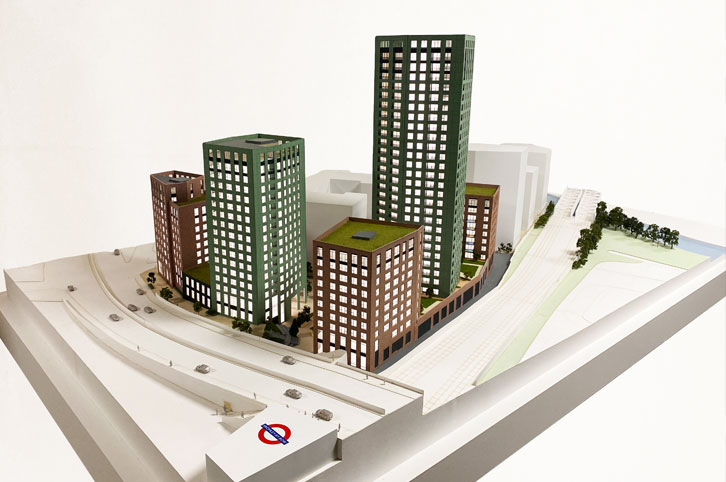 Architectural sales model 1:150 scale. Five highrise buildings painted green and brown brick. White offiste buildings. a tube station is in the foreground. Architectural model is animated with trees.