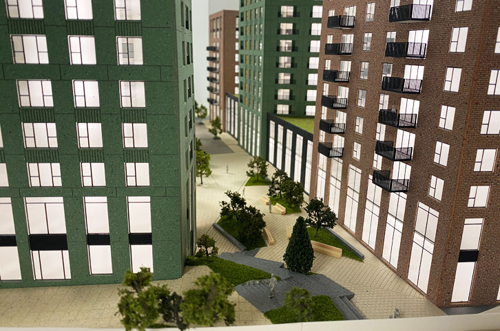 Close up image of an Architectural sales model, 1:150 scale. View down a raod inbetween two highrise buildings, painted green and brown brick. Roads are alser etched and animated wiht etched vellum trees.
