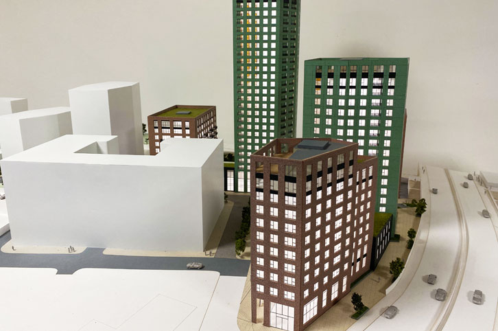 Architectural sales model 1:150 scale. Five highrise buildings painted green and brown brick. White offiste buildings. The architectural model is animated with trees.