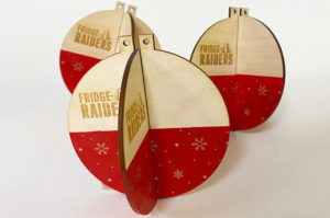Laser cut slot together Christmas baubles made from laser cut plywood. They are painted red and laser engraved with Fridge Raiders logo. .