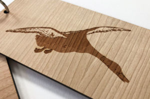 Close up of laser engraved duck on a hotel room key fob. Laser cut and etched from cherry wood laminated timber.